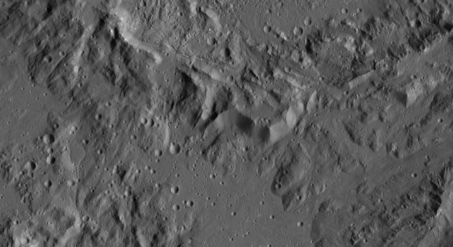 This image, taken by NASA's Dawn spacecraft, shows the rim of Ikapati Crater on Ceres. The rough features around the rim of this impact scar give way to smoother, lightly cratered terrain in the lower half of the image.