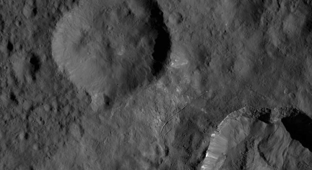This view from NASA's Dawn spacecraft shows an area in mid-southern latitudes on Ceres. The crater named Juling (12 miles, 20 kilometers wide) is seen at lower right. Bright material is visible along its upper walls.
