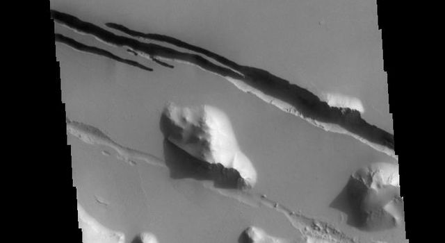 This image captured by NASA's 2001 Mars Odyssey spacecraft shows part of Cerberus Fossae. The linear depressions are called fossae.