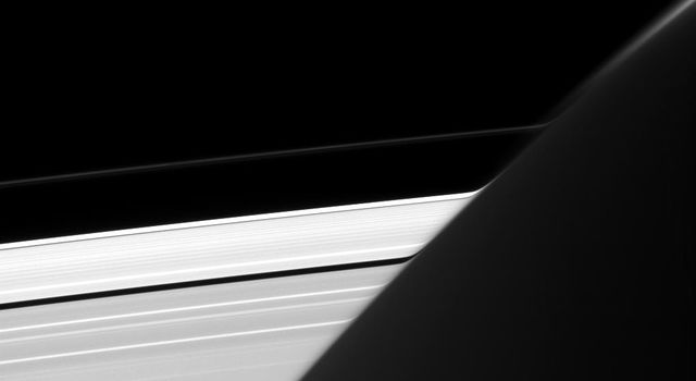 Captured by NASA's Cassini spacecraft, Saturn's A and F rings appear bizarrely warped where they intersect the planet's limb, whose atmosphere acts here like a very big lens.