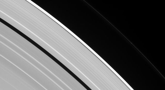 Two tiny moons of Saturn, almost lost amid the planet's enormous rings, are seen orbiting in this image from NASA's Cassini spacecraft. Pan, lower-right, is in the process of overtaking the slower Atlas, visible at upper-left.