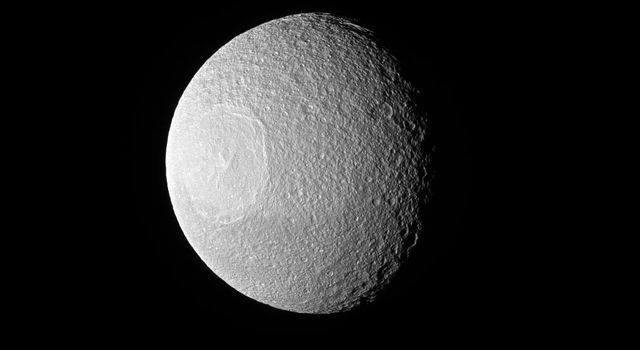 Tethys, one of Saturn's larger icy moons, vaguely resembles an eyeball staring off into space in this view from NASA's Cassini spacecraft. The resemblance is due to the enormous crater, Odysseus, and its complex of central peaks.