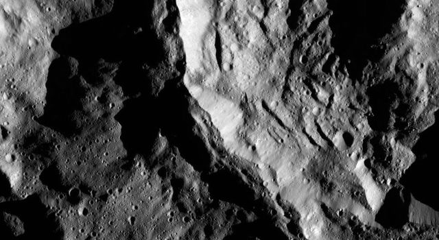 NASA's Dawn spacecraft shows Sekhet Crater on Ceres has prominent shadows accentuating its central peak and mounds of material that have slumped downward from its walls.