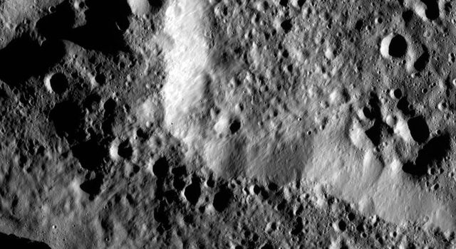 The rim of Hamori Crater on Ceres is seen in the upper right portion of this image, which was taken by NASA's Dawn spacecraft. Hamori is located in the southern hemisphere of Ceres and measures 37 miles (60 kilometers) wide.