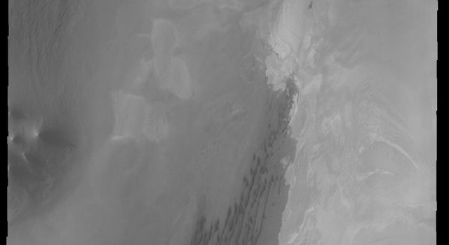 This image captured by NASA's 2001 Mars Odyssey spacecraft shows the north polar scarp, with the polar cap in the upper left corner.