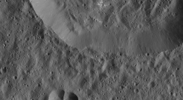 This image from NASA's Dawn spacecraft of Ceres shows a small, double-impact crater (at bottom) near a larger crater. The larger structure has a crater floor with roughly the same crater density.