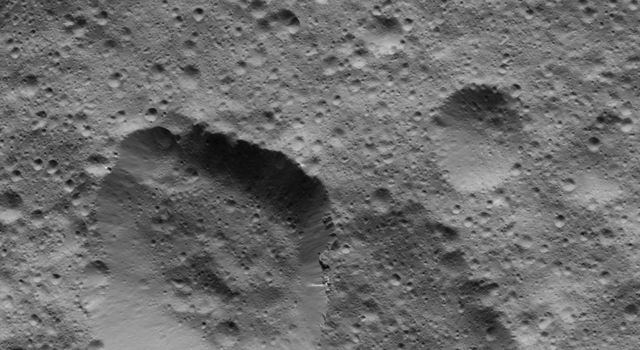 This picture from NASA's Dawn spacecraft shows craters in the northern hemisphere of Ceres. The large crater at lower left displays several bright streaks on its walls.