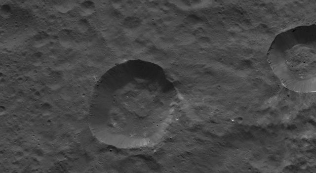 This picture from NASA's Dawn spacecraft shows craters near the equator of Ceres. Faint patches and streaks of bright material can be seen in various parts of the scene. The two largest craters have streaks of material on their walls.