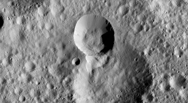 This picture from NASA's Dawn spacecraft shows terrain on Ceres in which the rim of a more recent impact crater, at center, has partially collapsed into its adjacent neighbor, just below. Boulders are visible in and around the younger, smaller crater.