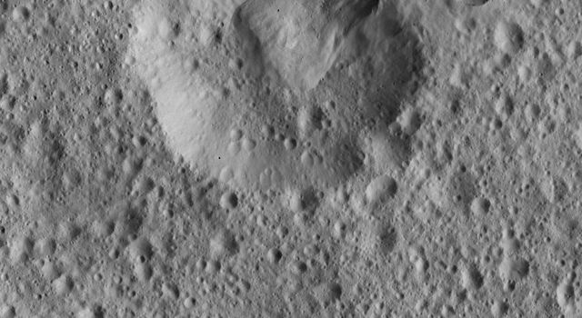 This view from NASA's Dawn spacecraft shows impact craters near Ceres' equator where material from the rim of one crater has apparently collapsed into its neighbor. A variety of large boulders are visible within the younger crater at top.