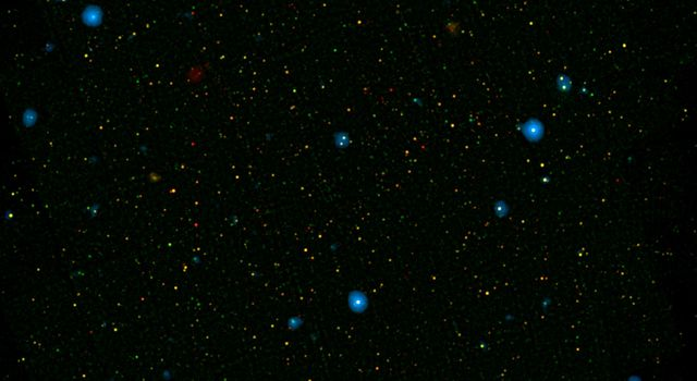 The blue dots in this field of galaxies, known as the COSMOS field, show galaxies that contain supermassive black holes emitting high-energy X-rays, as detected by NASA's Nuclear Spectroscopic Array, or NuSTAR.