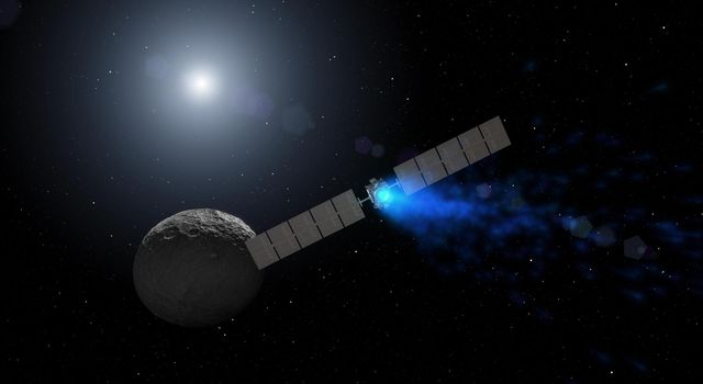 This artist's rendering shows NASA's Dawn spacecraft maneuvering above Ceres with its ion propulsion system. Dawn arrived into orbit at Ceres on March 6, 2015, and continues to collect data about the mysterious and fascinating world.