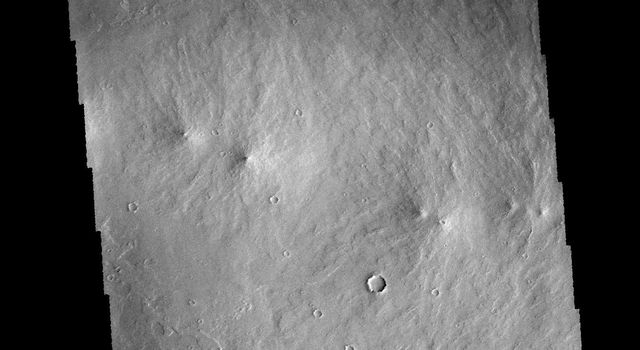 The 'tail' behind the crater at the top of this image from NASA's 2001 Mars Odyssey spacecraft is called a windstreak. This feature is formed by winds blowing over/in and around the crater.