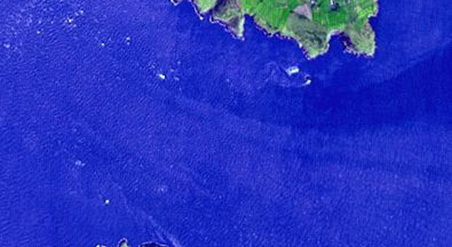 Lying 3 km off the Llyn peninsula of Wales, this image from NASA's Terra spacecraft shows Bardsey Island, known as the Island of 20,000 saints. While today's permanent population numbers only four, the island was once an important religious site.