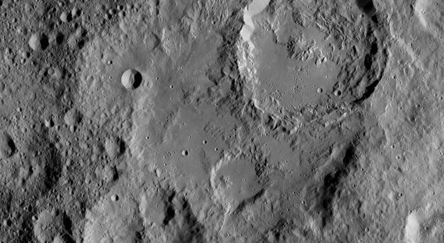 Ikapati Crater on Ceres is seen at top right in this image from NASA's Dawn spacecraft taken on Oct. 24, 2016. Ikapati has a complex of central peaks and roughly parallel fractures on its floor.