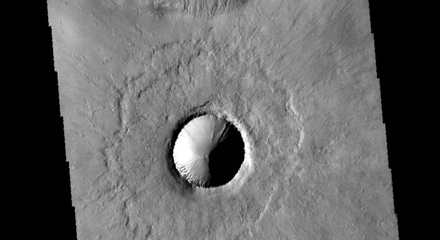 This image captured by NASA's 2001 Mars Odyssey spacecraft shows two craters in Terra Cimmeria just north of Kepler Crater. The small crater in the middle of the image is a relatively new crater.