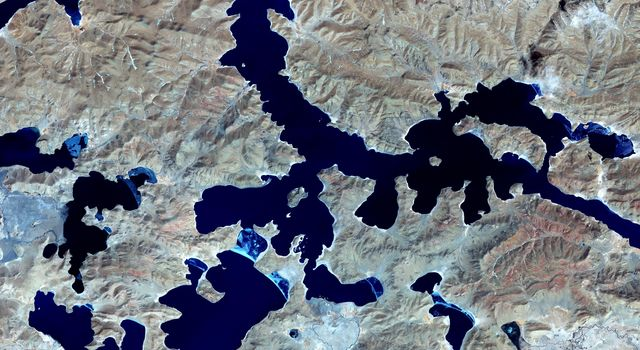 Yamzho Yumco (Sacred Swan) Lake in Tibet is surrounded by snow-capped mountains and is one of the three largest sacred lakes, as shown in this image from NASA's Terra spacecraft.
