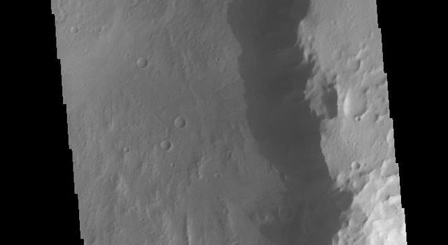 This image captured by NASA's 2001 Mars Odyssey spacecraft shows the sunrise shadow of the crater rim on the crater floor.