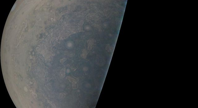 Cyclones swirl around the south pole, and white oval storms can be seen near the limb of Jupiter's south polar region taken by NASA's Juno spacecraft on Feb. 2, 2017.