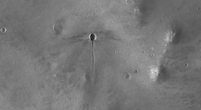 The broader scene for this image from NASA's Mars Reconnaissance Orbiter is the fluidized ejecta from Bakhuysen Crater to the southwest. A 'dragonfly' impact crater i seen with a gouged-out trench extending to the south.