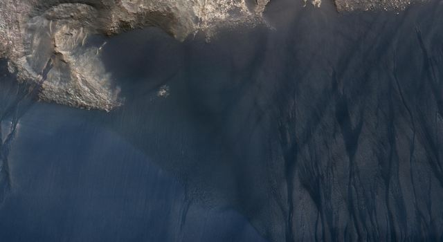 NASA's Mars Reconnaissance Orbiter spied this large crescent dune in Kaiser Crater showing the scars of many types of seasonal erosional activities.