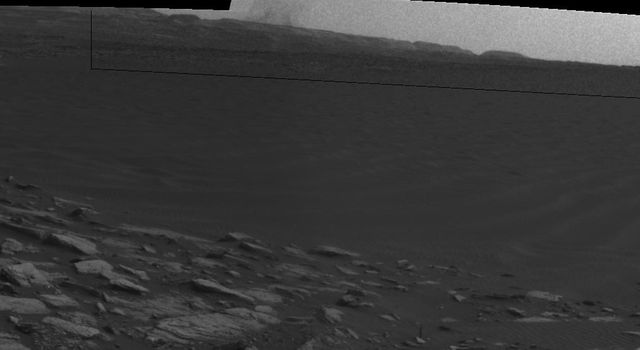 Beyond a dark sand dune closer to the rover, a Martian dust devil passes in front of the horizon in this frame from an animation from NASA's Curiosity Mars rover.