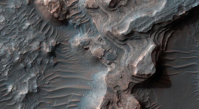 This image from NASA's Mars Reconnaissance Orbiter shows layered deposits in Uzboi Vallis which sometimes occur in alcoves along the valley and/or below where tributaries enter it.