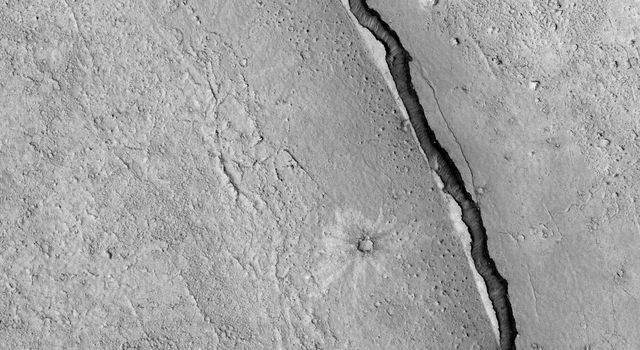 NASA's Mars Reconnaissance Orbiter spies a crater that lies close to Elysium, a major volcanic system on Mars. The whole region surrounding the crater was at some point covered by lava from the volcano creating vast lava plains.