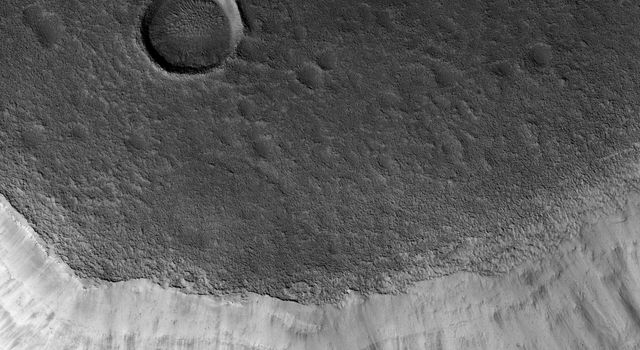 Mamers Valles is a long sinuous canyon beginning in Arabia Terra and ending in the Northern lowlands of Deuteronilus Mensae. This image from NASA's Mars Reconnaissance Orbiter features the southern facing slope of the canyon wall.