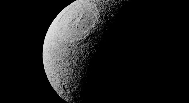 On Aug. 17, 2015, NASA's Cassini spacecraft captured this image of Odysseus crater with its ring of steep cliffs and the mountains that rise at its center, the most visually striking feature on Saturn's icy moon, Tethys.