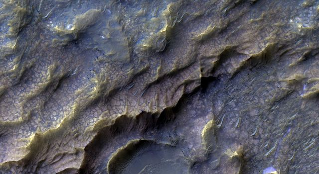 In this image from NASA's Mars Reconnaissance Orbiter, the pinkish, almost dragon-like scaled texture represents Martian bedrock that has specifically altered into a clay-bearing rock.