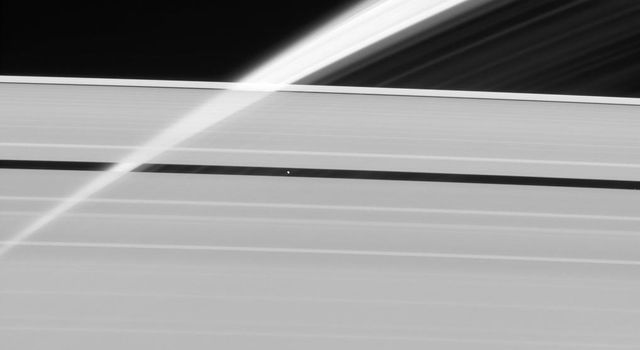 Saturn's rings, made of countless icy particles, form a translucent veil in this view from NASA's Cassini spacecraft. Saturn's tiny moon Pan orbits within the Encke Gap in the A ring.