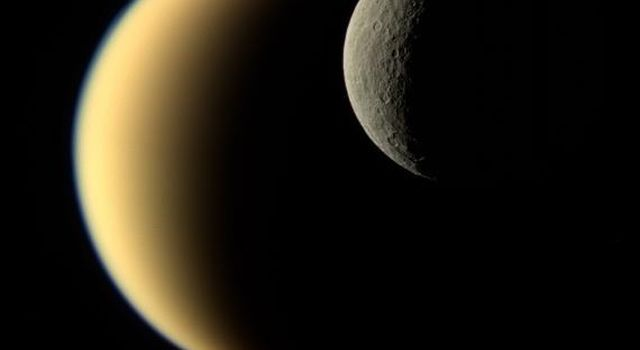 In this view, Saturn's icy moon Rhea passes in front of Titan as seen by NASA's Cassini spacecraft. While Rhea is a heavily-cratered, airless world, Titan's nitrogen-rich atmosphere is even thicker than Earth's.