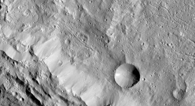 This image from NASA's Dawn spacecraft highlights Axomama Crater, the small crater shown to the right of center; its sharp edges indicate recent emplacement by a small impact.