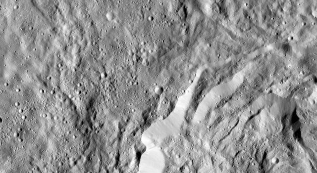 This image obtained by NASA's Dawn spacecraft shows a field of small craters next to Kokopelli Crater, seen at bottom right in this image, on dwarf planet Ceres.