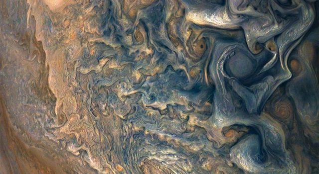 NASA's Juno spacecraft was a little more than one Earth diameter from Jupiter when it captured this mind-bending, color-enhanced view of the planet's tumultuous atmosphere.