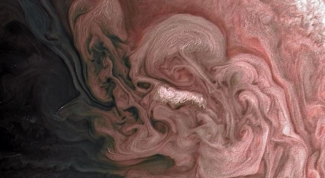 This image from NASA's Juno spacecraft captures a close-up view of a storm with bright cloud tops in the northern hemisphere of Jupiter, shown here in swirls of rose-colored hues.