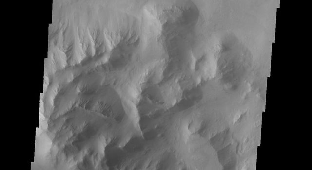 This image from NASA's 2001 Mars Odyssey spacecraft is located in central Coprates Chasma. The brighter materials at the bottom of the image are layered deposits. It is unknown how deep these canyon deposits were when they formed.