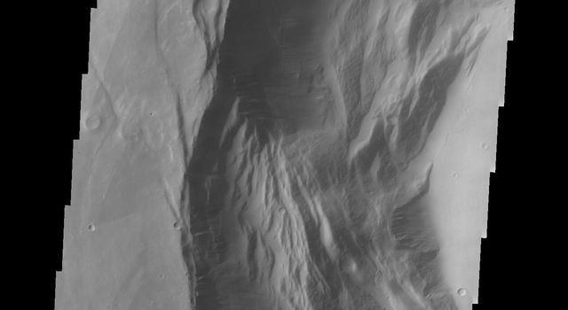This image from NASA's 2001 Mars Odyssey spacecraft shows the western part of the smaller summit caldera on Pavonis Mons. Pavonis Mons is one of the three aligned Tharsis Volcanoes.