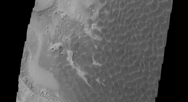 This image from NASA's 2001 Mars Odyssey spacecraft shows Rabe Crater. The appearance of the exposed side of the cliffs does not look like a volcanic, difficult to erode material, but rather an easy to erode material such as layered sediments.