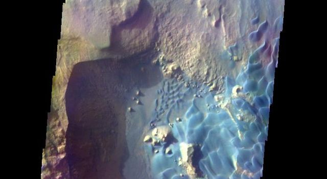 This is a false color image of Rabe Crater from NASA's 2001 Mars Odyssey spacecraft. In this combination of filters 'blue' typically means basaltic sand. Rabe Crater is 108 km (67 miles) across. Craters of similar size often have flat floors.