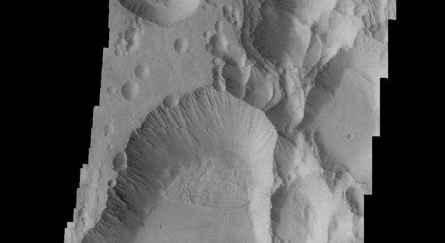The three large aligned Tharsis volcanoes are Arsia Mons, Pavonis Mons and Ascreaus Mons. This image from NASA's 2001 Mars Odyssey spacecraft shows part of the southern flank of Arsia Mons, along the center of the aligned fracture system.