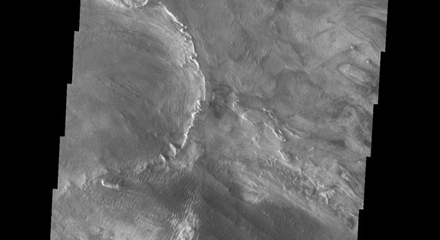 This image captured by NASA's 2001 Mars Odyssey spacecraft shows part of western Candor and the erosion of a large mesa. Layered materials are visible throughout the image.