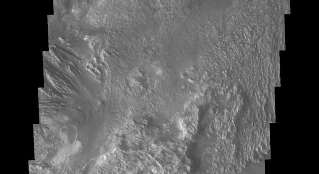 This image from NASA's 2001 Mars Odyssey spacecraft shows part of western Candor Chasma. Near the bottom of the image is an impact crater. Impact craters are relatively rare within all the canyons of Valles Marineria.