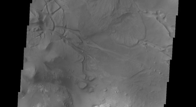 This image from NASA's 2001 Mars Odyssey spacecraft shows part of eastern Candor Chasma. At the top of the image is the steep cliff between the upper surface elevation and the depths of Candor Chasma.