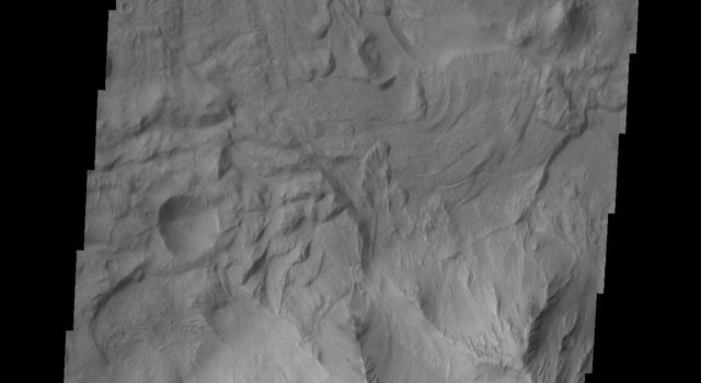 In this image of Tithonium Chasma from NASA's 2001 Mars Odyssey spacecraft both sides of the chasma are visible. This narrow and deep part of the chasma exist both large, chaotic block landslide deposits with smaller lobate shaped landslide deposits.
