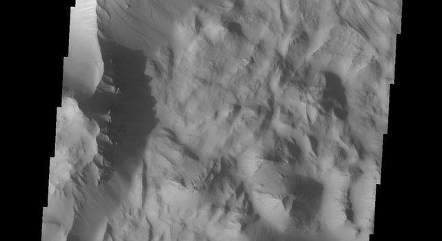 Continuing eastward along Ius Chasma, this section of the canyon floor has been completely filled by blocky deposits from large volume landslides. A landslide is a failure of slope due to gravity. This image captured by NASA's 2001 Mars Odyssey spacecraft