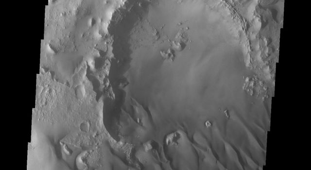The small crater in the middle of the image is at the upwind side of the dune field. There is a considerable amount of sand within the crater, with a relatively smooth surface and few dune forms. This image is from NASA's 2001 Mars Odyssey spacecraft.