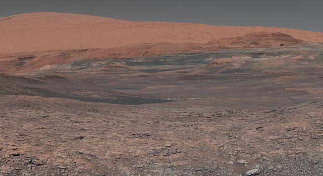This mosaic taken by NASA's Mars Curiosity rover looks uphill at Mount Sharp. The scene has been white-balanced so the colors of the rock materials resemble how they would appear under daytime lighting conditions on Earth.