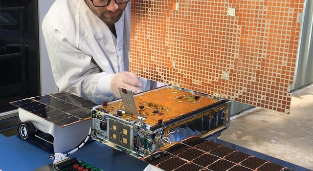 Engineer Joel Steinkraus uses sunlight to test the solar arrays on one of the Mars Cube One (MarCO) spacecraft at NASA's Jet Propulsion Laboratory.